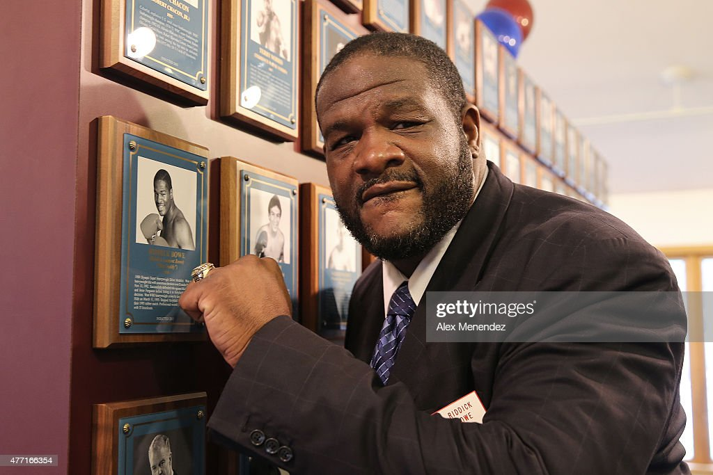 Boxing champion Riddick Bowe poses with his new ring and photo on the wall after the induction ceremony at the International Boxing Hall of Fame induction Weekend of Champions events on June 14, 2015 in Canastota, New York.
