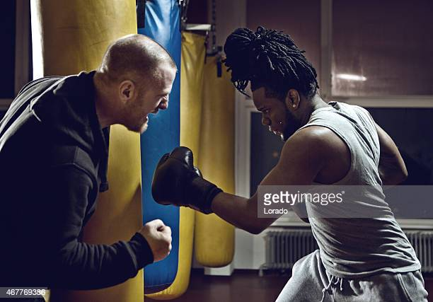 boxing coach shouting at boxer practicing with punch bag