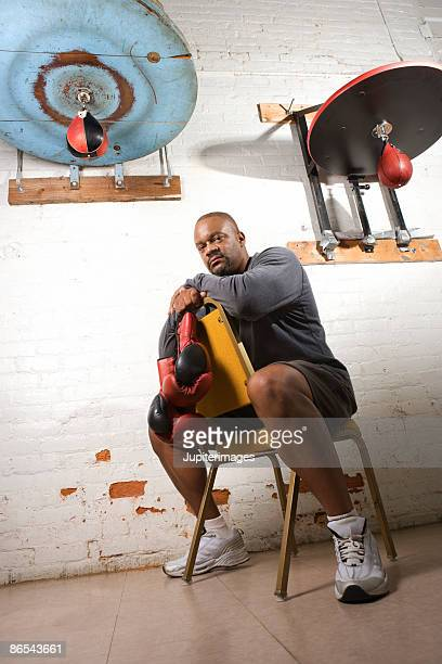 Boxing coach sitting in gym