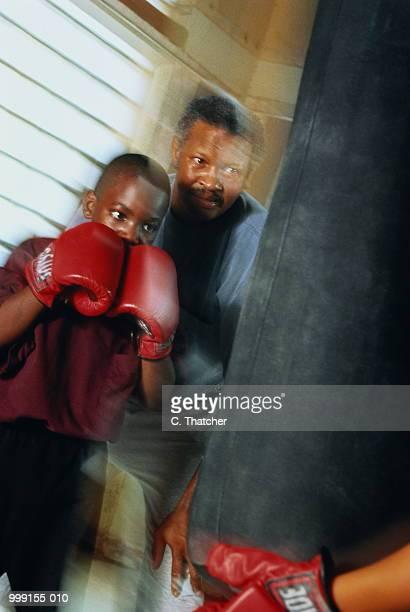 Boxing coach teaching boy (9-11) how to box on punching bag