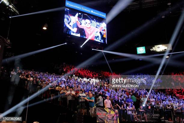 Boxing fans cheer during the official weighin of British boxer Tyson Fury and US boxer Deontay Wilder ahead of their heavyweight fight at the MGM...