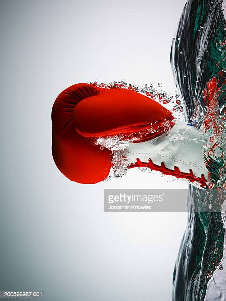 Boxing glove emerging from water in form of clenched fist