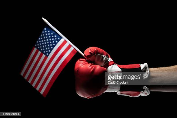boxing glove holding an american flag - punching stock pictures, royalty-free photos & images