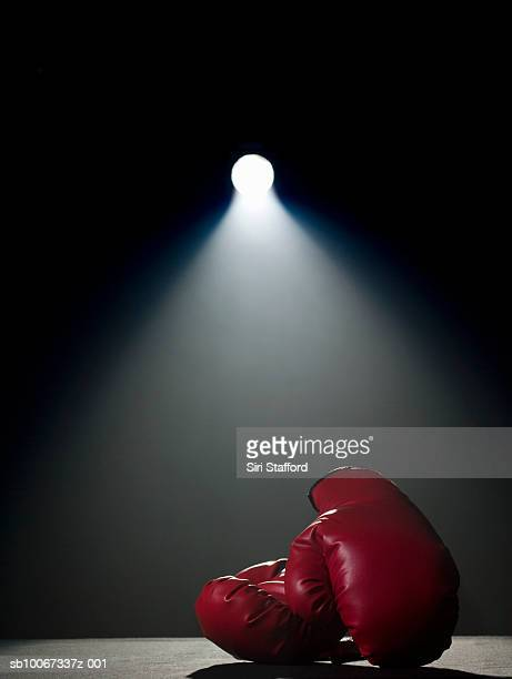 boxing gloves in spotlight - boxing gloves stock photos and pictures