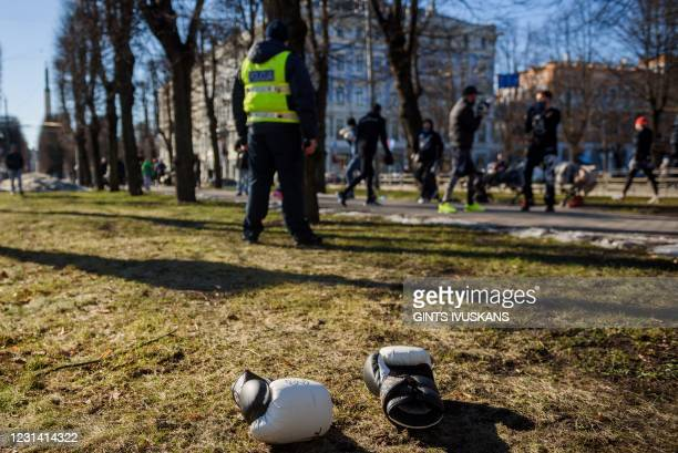 Boxing gloves lie on the grass as athletes, boxers and fitness trainers take part in an open air training as a protest form against coronavirus...