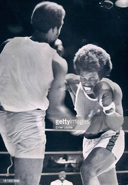 MAR 28 1974 Boxing Golden Gloves Simultaneous Connection George Clark of Knoxville Tenn sends a right to the stomach of Larry Martin of Kansas City...