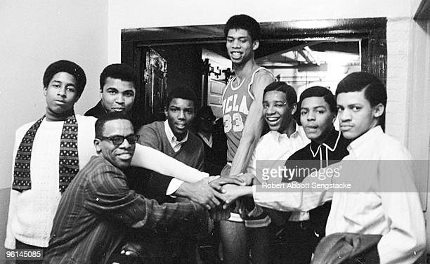 Boxing great Muhammad Ali back row second from left poses with a group of young men among them basketball great Kareem Abdul Jabbar back row center...