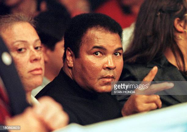 Boxing great Muhammad Ali gestures to photographers as he sits at ringside before the match of his daugher Laila Ali of Los Angeles and April Fowler...