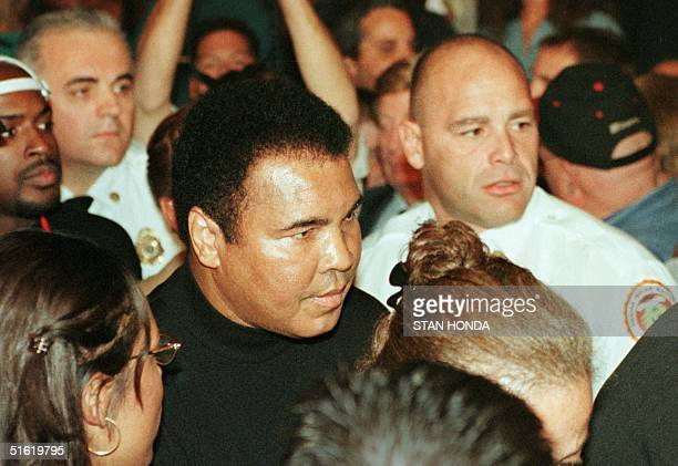 Boxing great Muhammad Ali makes his way through a crowd at ringside to watch his daughter Laila Ali make her professional boxing debut against April...