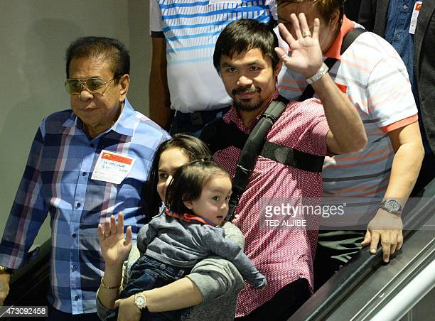 Boxing icon Manny Pacquiao of the Philippines and his wife Jinkee wave to photographers shortly after arriving from the US at the international...