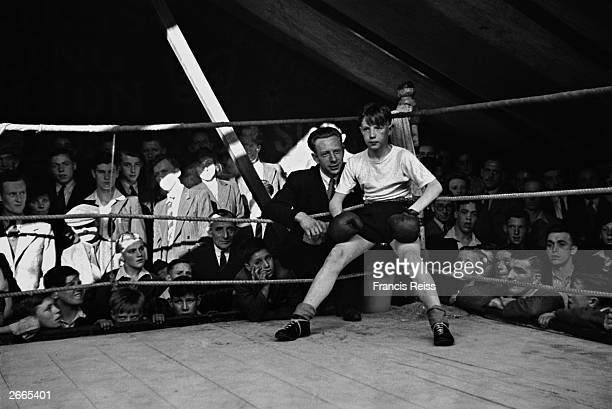 A boxing instructor coaches his young pupil in the Hughes of London boxing pavilion at a Lancashire fair Original Publication Picture Post 2046 Where...