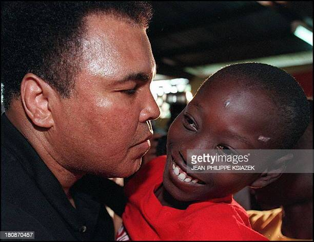 Boxing legend and former World champion Muhammad Ali carries a Liberian warmutilated child 20 August in San Pedro as he visits a refugee camp Ali on...