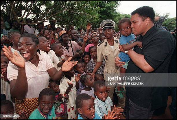 Boxing legend and former World champion Muhammad Ali carrying a child is welcomed upon arrival 20 August in San Pedro where 437 Liberian refugees...