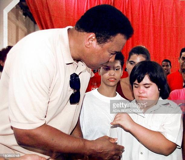 US boxing legend Muhammad Ali greets a young Cuban girl suffering from Downs Syndrome during his visit to the Cerro Pelado sport complex 10 September...