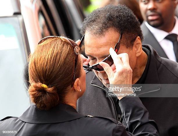 Boxing legend Muhammad Ali has his sunglasses adjusted by his wife Lonnie as he arrives at Ricky Hatton's gym as part of his Uk charity tour on...