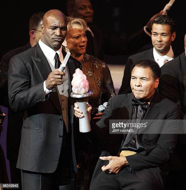 US boxing legend Muhammad Ali holds a flame with former heavyweight champion Evander Holyfield 19 November 2005 during the Grand Opening Gala for the...
