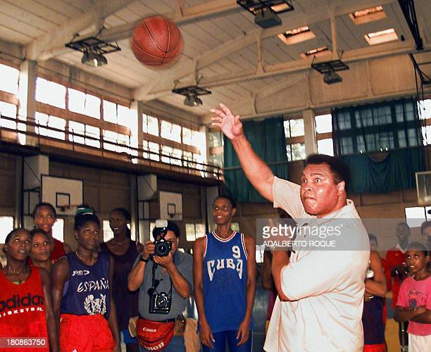 US boxing legend Muhammad Ali shoots a basketball towards the basket under the watchful eyes of members of the Cuban women's basketball selection at...