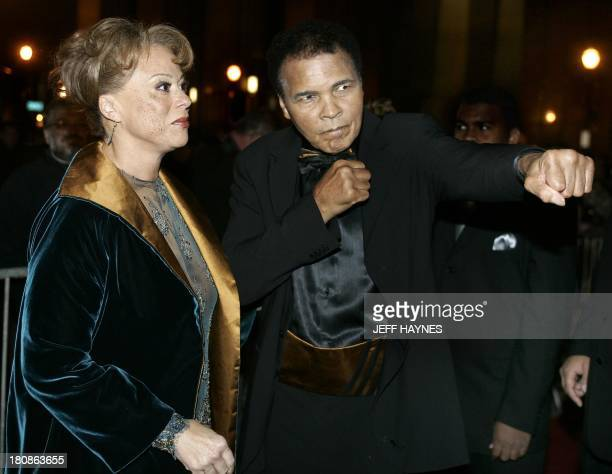 US boxing legend Muhammad Ali strikes a boxing pose on the red carpet with his wife Lonnie 19 November 2005 before the Grand Opening Gala for the...