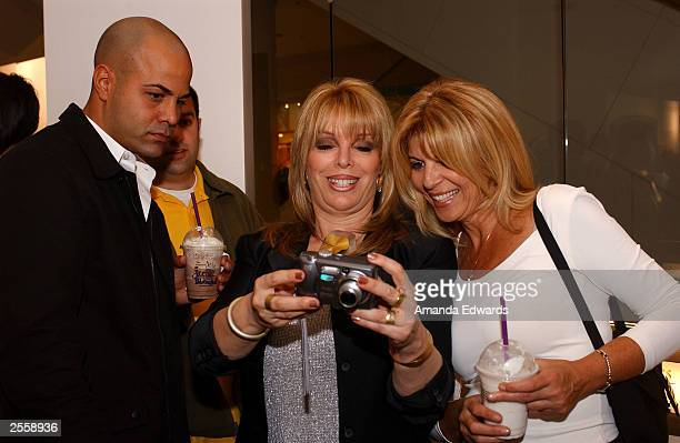 Boxing manager Jackie Kallen looks at photos with boxer Tarick Salmaci and Malka Winshman at the Knockout Preview Party hosted by Jackie Kallen and...