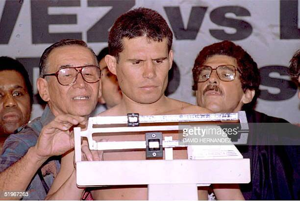 Boxing officials look over the shoulder of Julio Cesar Chavez of Mexico 9 December as he weighs in for his 10 December WBC Super Lightweight title...
