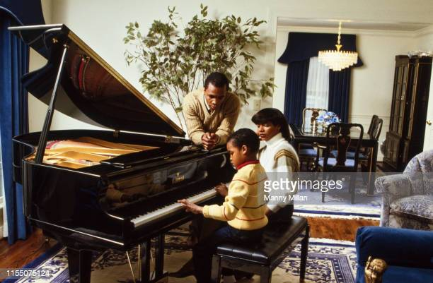 Portrait of Sugar Ray Leonard with his son Ray Charles Leonard Jr and wife Juanita Wilkinson playing the piano in their Maryland home CREDIT Manny...