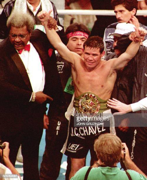 Boxing promoter Don King helps raise WBC superlightweight boxing champion Julio Cesar Chavez's hands in victory after Chavez defeated challenger...