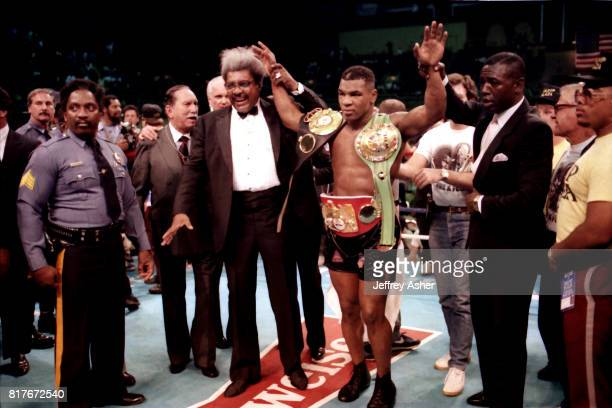 Boxing Promoter Don King holds up Boxer Iron Mike Tyson's hand in victory with his championship belt after knocking out Opponent Michael Spinks at...