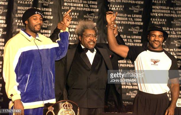 Boxing promoter Don King raises the arms of WBC Heavyweight Champion Lennox Lewis of Britain and WBA/IBF Champion Evander Holyfield of the USA during...