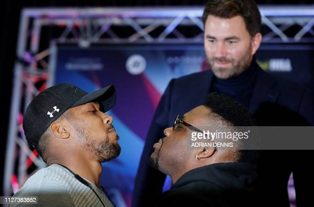 Boxing promoter Eddie Hearn watches as British boxer Anthony Joshua and US boxer Jarrell Miller pose during a joint press conference in London on...