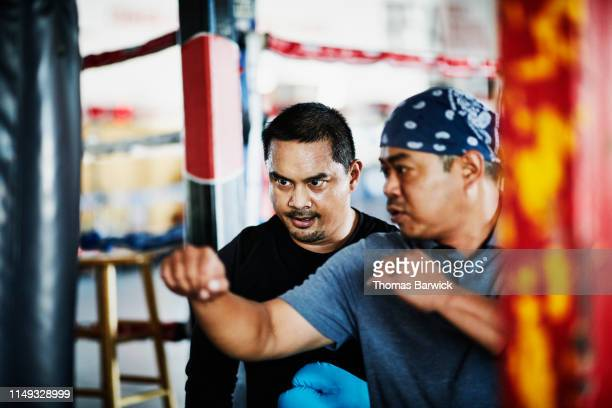 Boxing trainer demonstrating technique to boxer working out on heavy bag in gym
