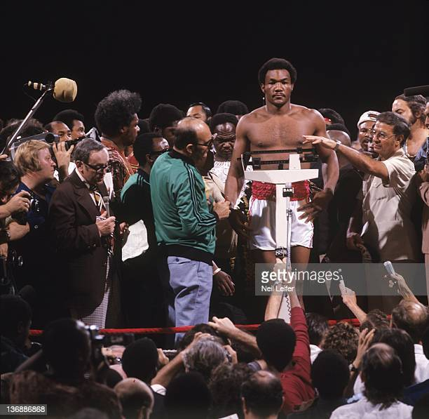Boxing: WBC/ WBA World Heavyweight Title: George Foreman during weigh-in as Angelo Dundee works the scale before fight vs Muhammad Ali at Stade du 20...