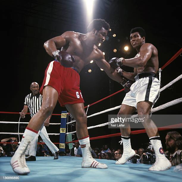 Boxing: WBC/ WBA World Heavyweight Title: Muhammad Ali in action, taking punch from George Foreman against the ropes during fight at Stade du 20 Mai....