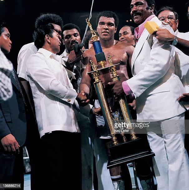 Boxing WBC/ WBA World Heavyweight Title Muhammad Ali victorious receiving trophy from Filipino President Ferdinand Marcos after winning fight vs Joe...