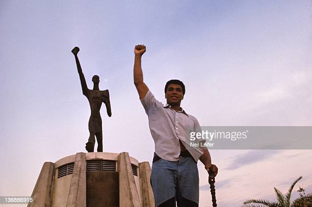 Boxing: WBC/ WBA World Heavyweight Title Preview: Portrait of Muhammad Ali posing in front of Le Militant statue before fight vs George Foreman at...