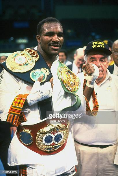 Boxing WBC/WBA/IBF Heavyweight Title Evander Holyfield victorious with trainer Lou Duva and trophy belt after winning fight vs George Foreman at...