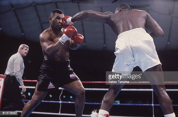 Boxing WBC/WBA/IBF Heavyweight Title Mike Tyson in action taking punch vs James Buster Douglas at Tokyo Dome Tokyo Japan 2/11/1990