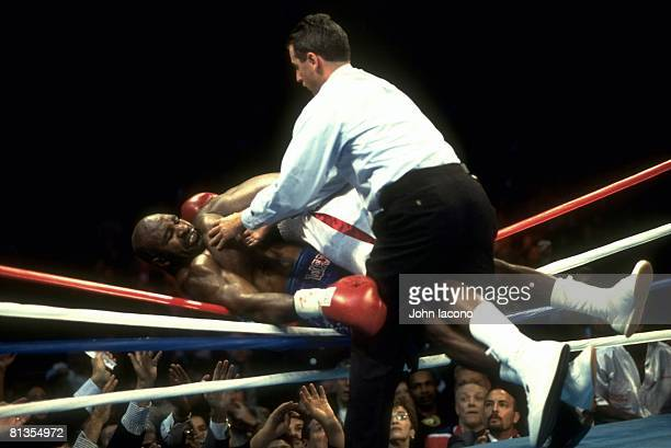 Boxing WBC/WBA/IBF/IBO Heavyweight Title Lennox Lewis in action pushing Evander Holyfield out of ring at Thomas Mack Center View of referee Mitch...