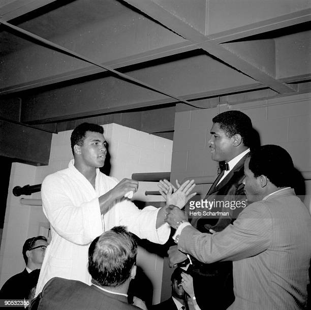World Heavyweight Title Muhammad Ali arguing wtih next opponent Ernie Terrell in locker room after fight vs Cleveland Williams at Astrodome Houston...