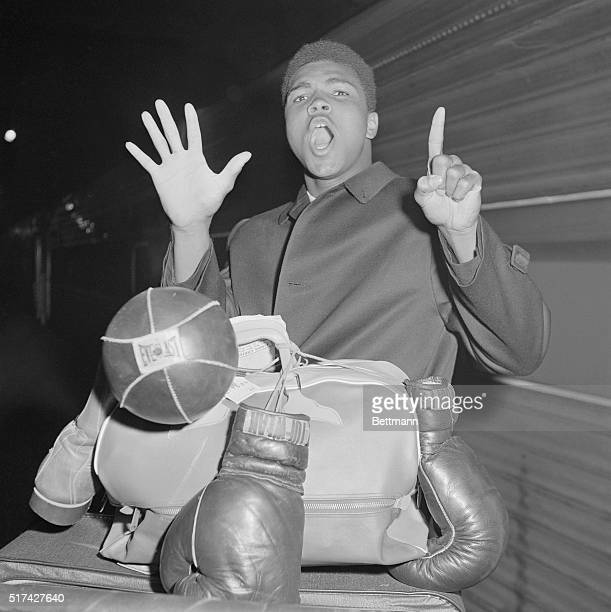Boxing's flamboyant Cassius Marcellus Clay sporting a porter's cap mugs it up while showing his name on fight card to porter Herbert Sims here March...