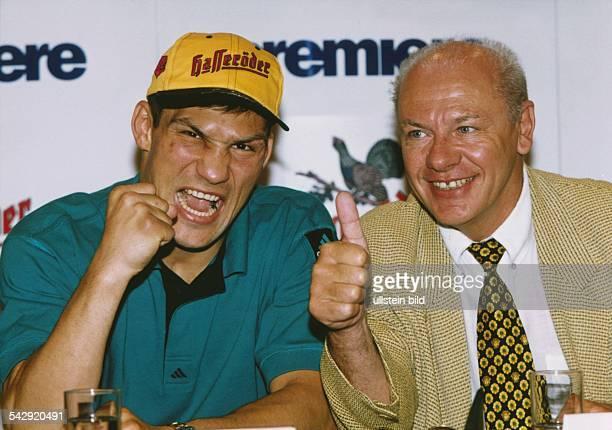 Boxprofi Dariusz Michalczewski genannt der Tiger sitzt mit geballter Faust aufgerissenem Mund und BaseballKappe mit HasseröderWerbung neben dem...