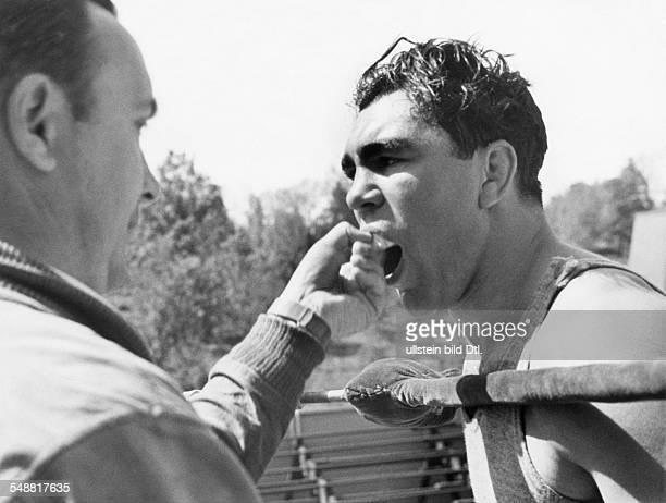 Boxsportler D erhaelt von Trainer Machon den Mundschutz bei der Vorbereitung auf den Kampf gegen James J Braddock Mai 1937