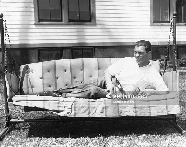 Boxsportler D liest Zeitung auf einer HollywoodSchaukel 1930