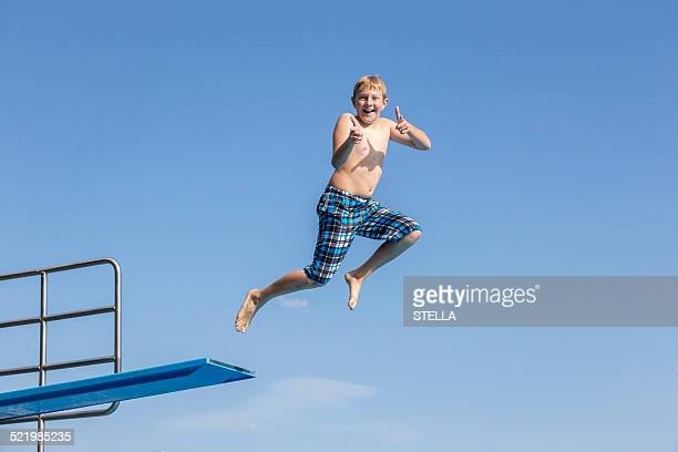 Boy, 10 years, jumping from a three-meter board making a thumbs up gesture