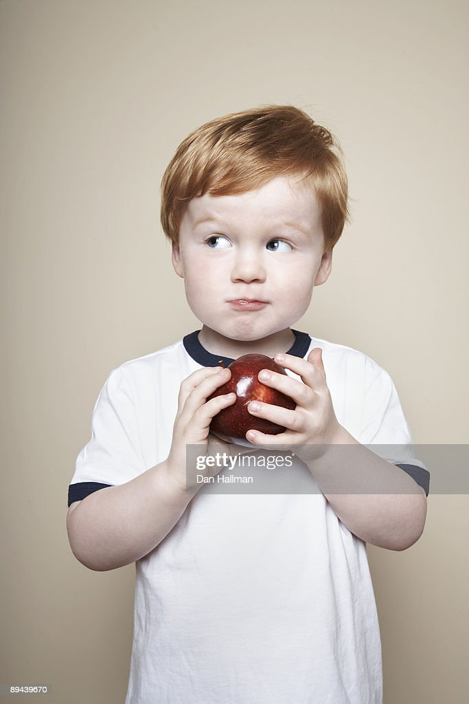 Boy, 3 years old, holding an apple. : Stock Photo