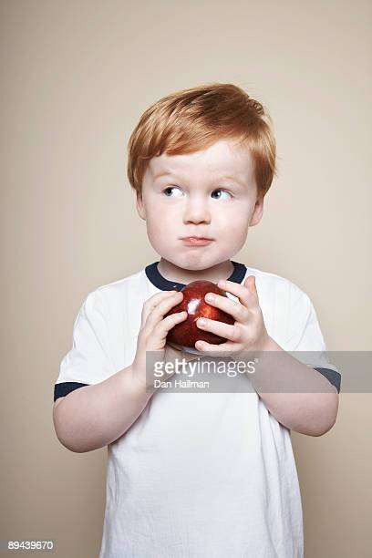 Boy, 3 years old, holding an apple.