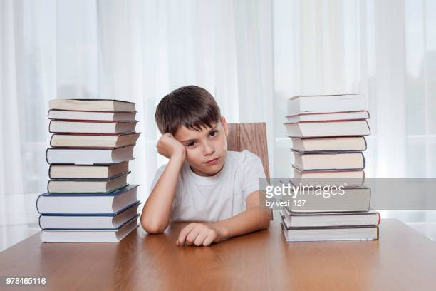 boy, 8-9 years, looking bored surrounded by stacks of books - 6 7 years stock pictures, royalty-free photos & images