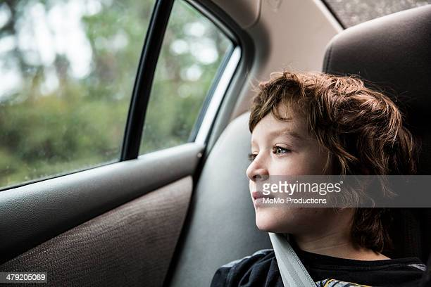 Boy (9 in backseat of car, looking out window