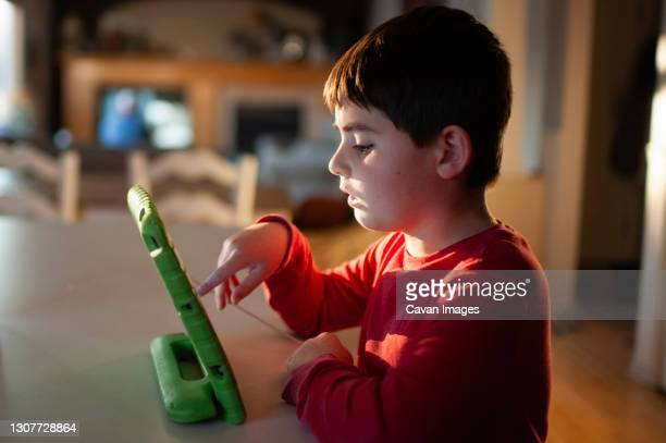 boy 9-10 years old playing with his tablet at the kitchen counter - 12 13 years stock pictures, royalty-free photos & images