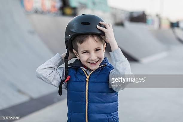 Boy adjusting his safety helmet