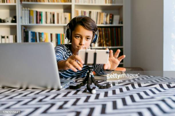 boy adjusting smart phone on tripod sitting by laptop at table - primary age child stock pictures, royalty-free photos & images